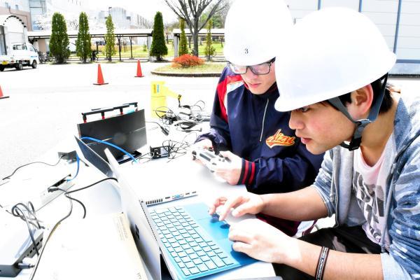 神ノ門真吾さん(左)が真剣な表情でロボットを操作していた。微妙な操作が求められるという=会津若松市一箕町の会津大