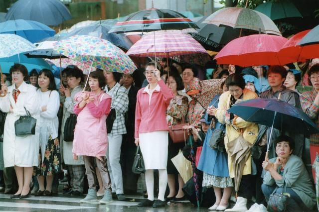 傘をさし雨の中で党首の第一声を聞く人たち。1996年秋の第41回総選挙は中選挙区制に代わって小選挙区比例代表並立制が採用され、最初の選挙となった=1996年10月8日