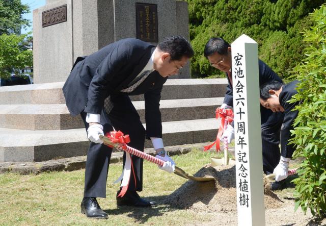 池田勇人元首相の銅像前で記念植樹する岸田文雄・宏池会会長=2017年5月28日、広島市中区
