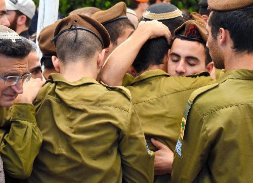 「最も悲しい写真」が投稿された同じ頃、死亡した兵士の慰霊式で、戦友の死に肩を抱き合って慰め合うイスラエル兵たち=2014年7月23日、エルサレム、仙波理撮影