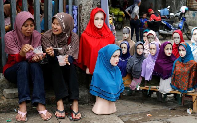 ヒジャブを売る売店と、並んで座る女性たち。インドネシアの首都ジャカルタで=2014年6月27日