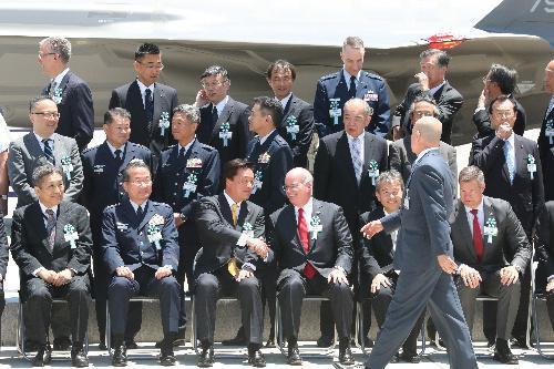 公開されたF35A戦闘機の前で記念撮影後、ロッキード・マーティン社の代表と握手する若宮健嗣防衛副大臣=5日午後、愛知県豊山町、吉本美奈子撮影