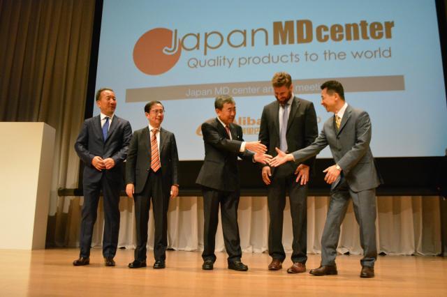 新たに提携を始めたカルビーの松本晃会長(中央)と記念撮影に臨むダニエル・チャン氏(左から2人目)。穏やかな笑みを絶やさない=5月25日