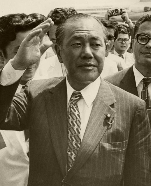 右手を挙げ得意のポーズをとる田中角栄氏