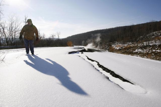 溝ができた61道路の側を歩く「ペンシルベニア州廃坑再生機構環境保護局」の職員=セントラリア、2007年12月