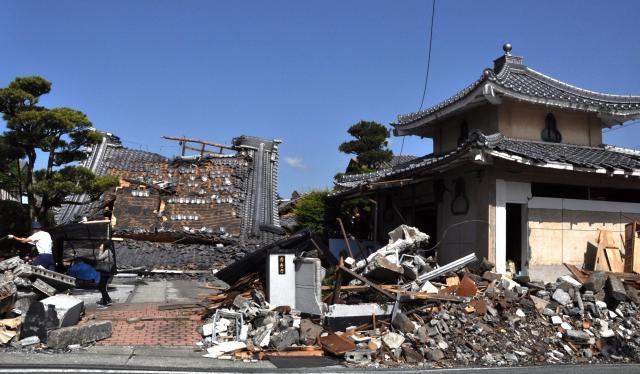 熊本地震で本堂(左)が倒壊し、納骨堂(右)も損壊した寺=熊本県益城町(2016年4月)