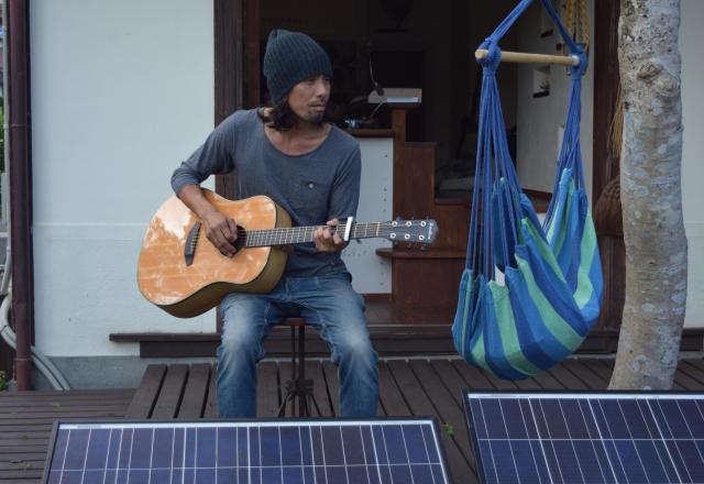 自宅にある太陽光パネルの前で、ギターを弾く東田さん=熊本市