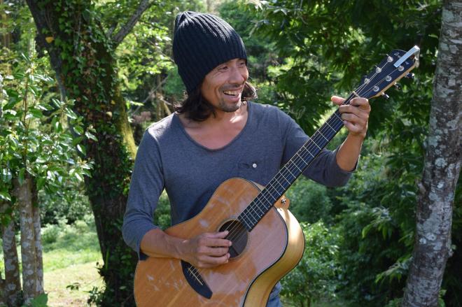 ギターを手にする東田トモヒロさん。取材場所となったご自宅は、緑に囲まれていた=熊本市
