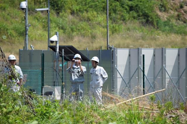 石木ダム計画の付け替え道路工事の様子を写真撮影していると、作業服を着た男性からビデオカメラを向けられた=長崎県川棚町