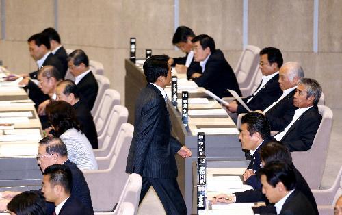ヤジ関連の決議案の採決前、自席を離れる鈴木章浩都議=2014年6月25日、都議会、嶋田達也撮影