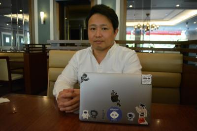 泉幸典さん。パソコンにはロボットたちのシールが貼られている=東京都港区
