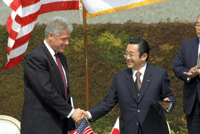 1996年4月、日米首脳会談で共同宣言の調印式で署名した後、クリントン米大統領(左)と握手する橋本龍太郎首相=東京・元赤坂の迎賓館で
