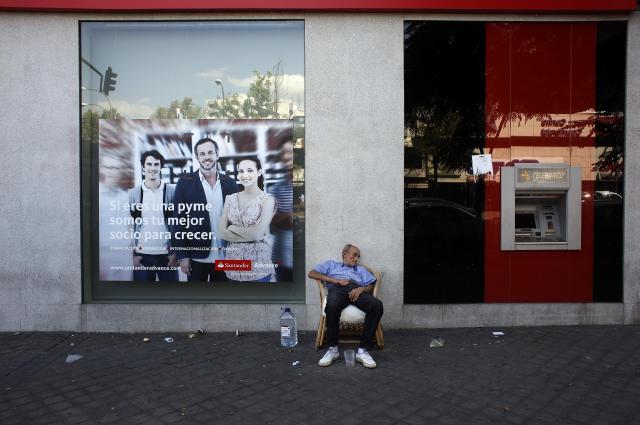銀行支店の前でシエスタ中の物乞いのお年寄り=2014年9月、マドリード・スペイン