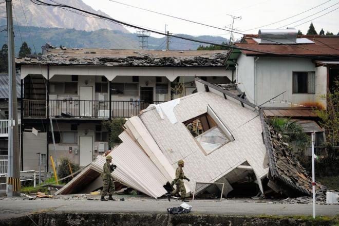 熊本地震で倒壊した建物周辺を歩く自衛隊員=2016年4月16日、熊本県南阿蘇村、長沢幹城撮影