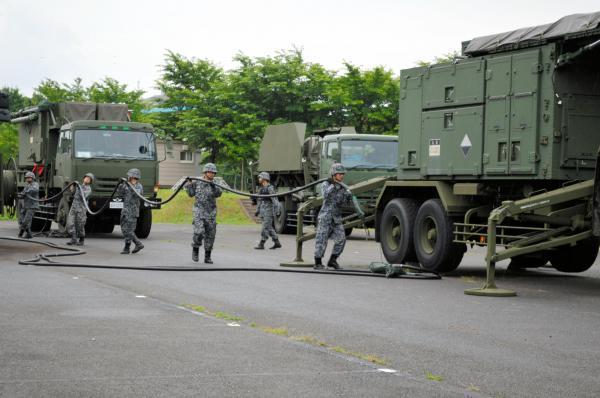 車両に載せたレーダー(右)に電源車からのケーブルをつなぐ航空自衛隊員ら=21日午前7時前、陸自朝霞駐屯地駐車場、藤田直央撮影
