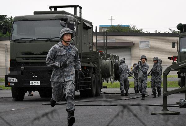 電源車からコードをのばす自衛隊員=21日午前6時50分、陸上自衛隊朝霞駐屯地、角野貴之撮影