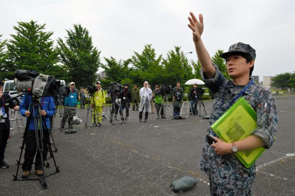 「あちらの方は撮らないでください」と報道陣に説明する航空自衛隊の広報担当者=21日午前6時50分ごろ、陸自朝霞駐屯地駐車場、藤田直央撮影