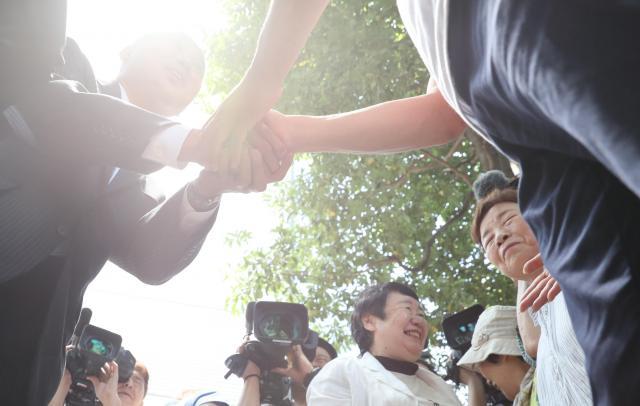 有権者(左)と握手する都議選候補者=23日午前、都内、西畑志朗撮影