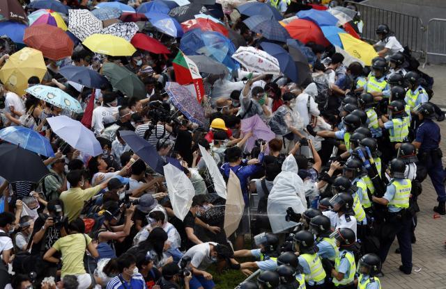 警察の放射する催涙スプレーを傘で受け止めるデモ隊=2014年9月28日