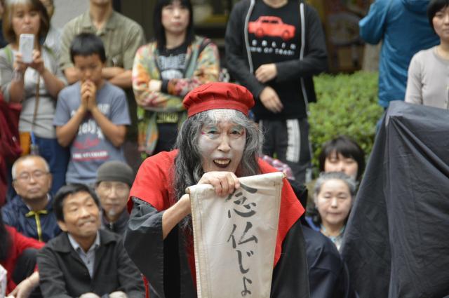 「念仏じょんがら」と書かれた布を掲げるギリヤークさん=2016年、東京・西新宿