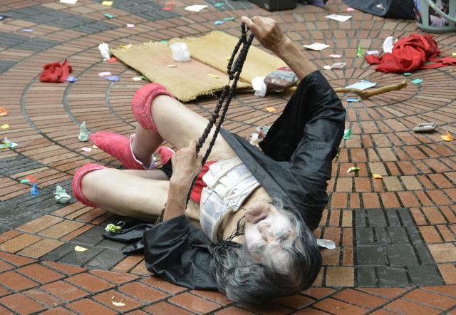 地面に身体を投げ出して踊るギリヤークさん=2016年、東京・西新宿