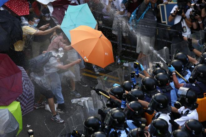 香港の中心部に集まった若者たちを、催涙スプレーで追い払おうとする警察。79日間にわたる香港「雨傘革命」の始まり=2014年9月28日