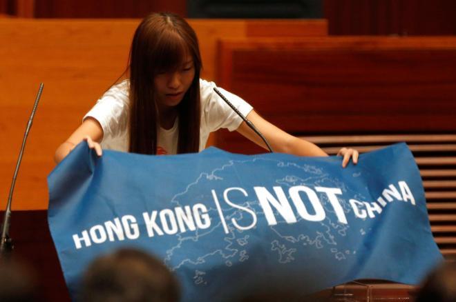 香港独立を視野に入れる「青年新政」から立法会の議員に当選し、議場で「香港は中国ではない」と書いた横断幕を広げる游蕙禎さん。後に逮捕された=2016年10月12日