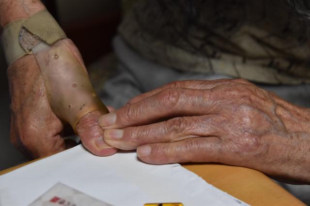 警察で母印をとった際の様子を再現するギリヤークさん。「5本指全部。指の上から強く押しつけられるようにしてとりました」