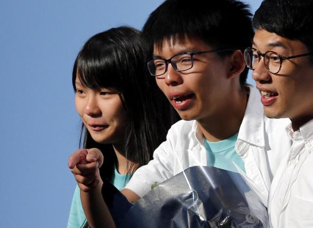 新党「香港衆志」から立法会議院に当選したネイサン・ロー(羅冠聰)さん(右)とともに、笑みを浮かべるアグネスさん(左)。中央はジョシュアさん=2016年9月5日