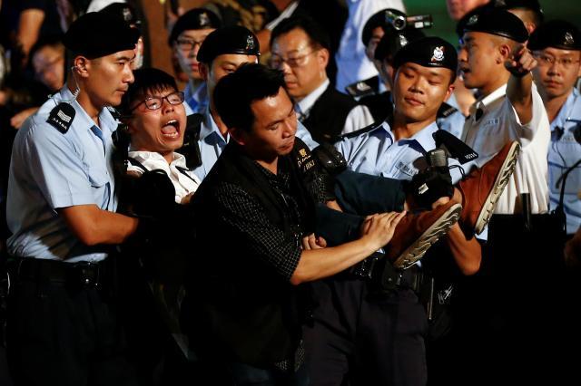 香港返還を記念して中国政府が贈ったモニュメントで抗議活動をし、警察に逮捕、連行されるジョシュアさん=2017年6月28日