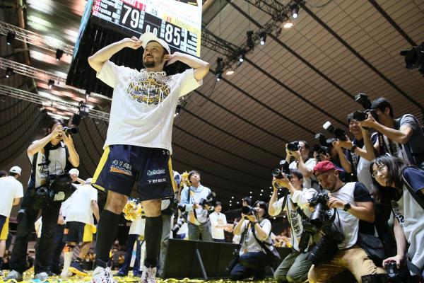 ゴールネットをかぶった田臥選手を多くの報道陣が取り囲んだ=2017年5月27日、東京・国立代々木競技場、西畑志朗撮影