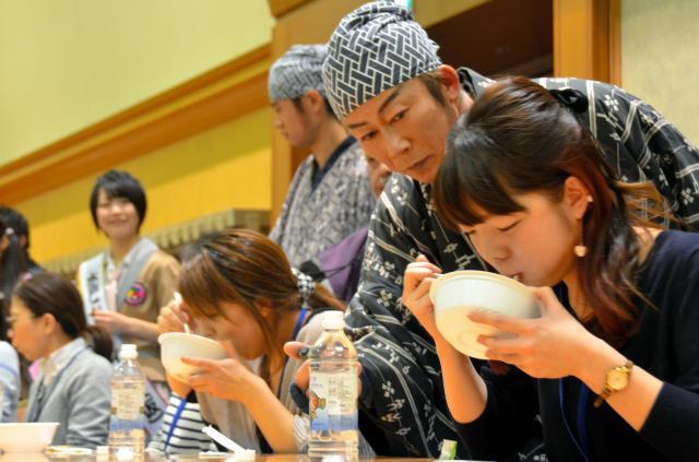 早食い大会で納豆をかきこむ参加者たち=2015年2月28日、水戸市