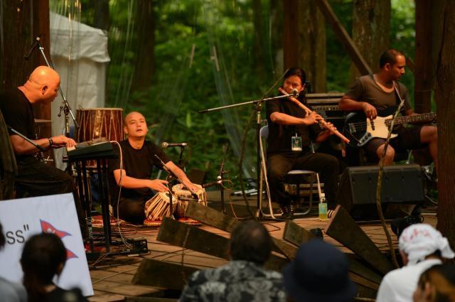 自然に囲まれたステージで心地よい太鼓と笛の音色を響かせた、ネパール出身の「ウペンドラ・アンド・フレンズ」=2015年