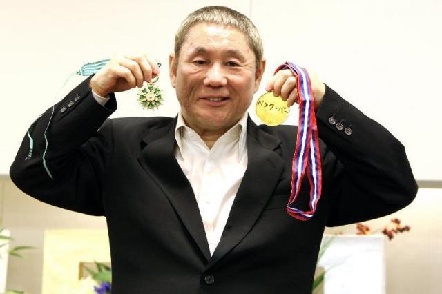 仏の勲章「コマンドール章」のメダル(左)と手製の「金メダル」を手に、笑顔を見せる北野武さん=成田空港、2010年3月