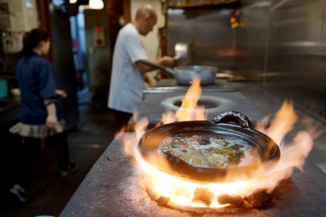 炎に包まれるスッポン鍋=京都市上京区