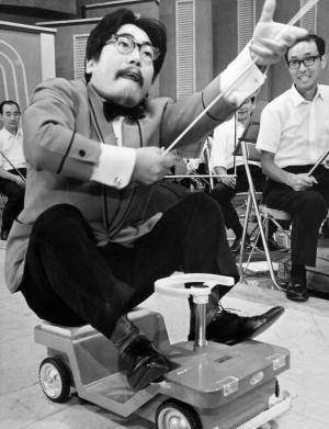 おもちゃの自動車に乗ってタクトを振る山本直純=1967年