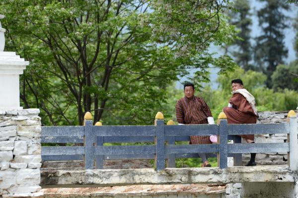 県庁であるパロ・ゾンにつながる橋の手前で話し込む民俗衣装「ゴ」を来た男性たち=2017年6月5日、ブータン・パロ、北村玲奈撮影