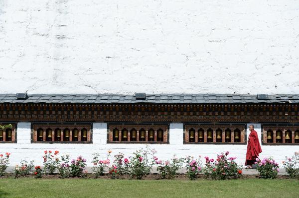 タシチョゾンの中庭に飾られたマニ車の前を歩く僧侶=2017年6月2日、ティンプー・タシチョゾン、北村玲奈撮影