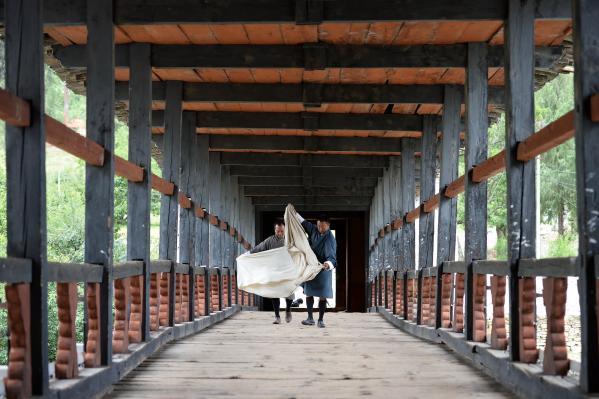 県庁であるパロ・ゾンへつながる橋を歩く民族衣装「ゴ」を着た男性。正装の際に必要な白い布を広げている=2017年6月5日、ブータン・パロ、北村玲奈撮影