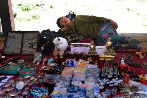 タクツァン僧院のふもとに開かれたお土産屋。観光客で賑わっているにもかかわらず、店主は昼寝をしていた=2017年6月6日、ブータン・パロ、北村玲奈撮影
