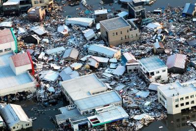 東日本大震災で津波に流された家が折り重なる気仙沼港周辺の市街地。2011年3月12日、宮城県気仙沼市