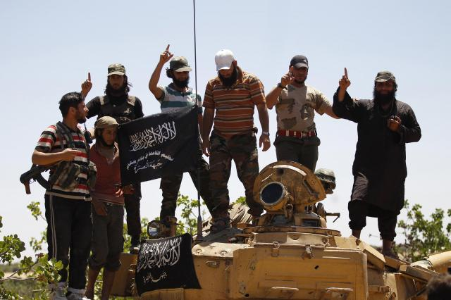 シリア北西部イドリブ県で、人さし指を突き上げるヌスラ戦線(現・シャーム解放委員会)のメンバー=2014年5月17日