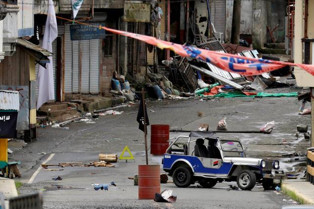 マウテグループが占領するフィリピン南部マラウィの一地区。ドラム缶の上に立てられているのはISの黒い旗=2017年5月29日