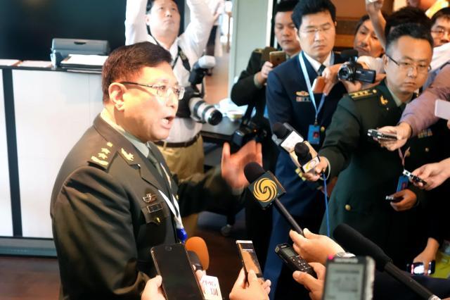 報道陣に囲まれて中国側の立場を主張する中国代表団長の何雷氏(左)=シンガポール、6月3日、西村大輔撮影