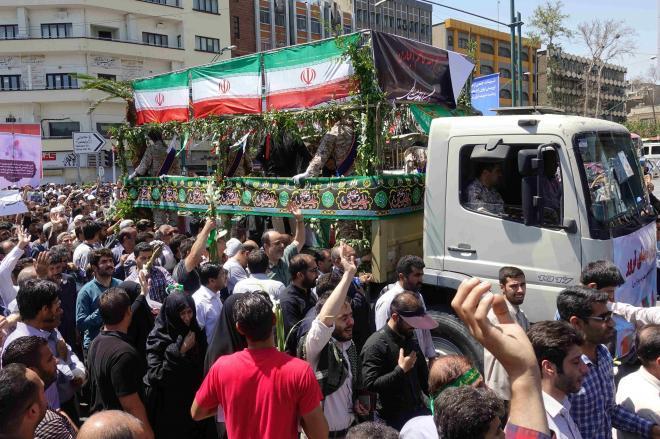 テロ犠牲者の棺を運ぶトラックのまわりで、「ISくそったれ」「サウジと米国に死を」と叫びながら行進するテヘランの市民=6月9日、杉崎慎弥撮影