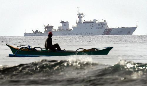 漁をするフィリピン人漁師の奥には中国の船が監視するように停泊していた=2016年12月、矢木隆晴撮影