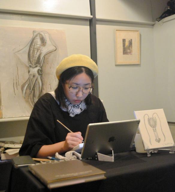 イカの図鑑を見ながらイカ墨で絵を描く宮内さん=鹿児島市