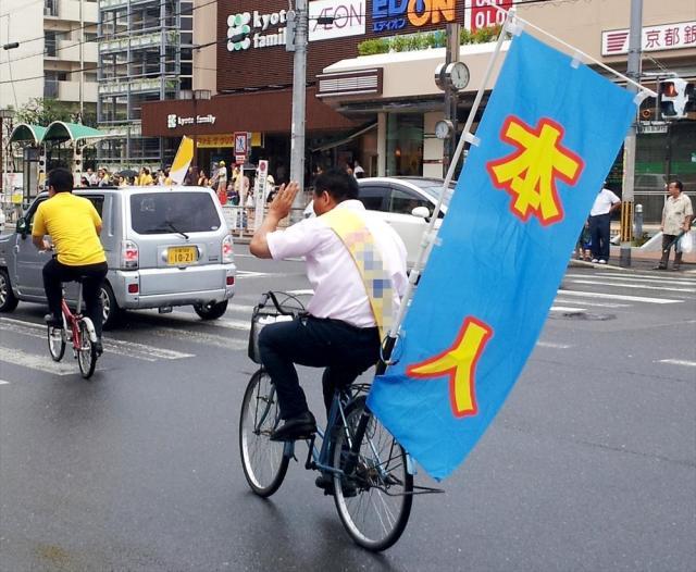 2013年の参院選で「本人」と書いた旗とともに自転車に乗って支持を訴える候補者=2013年7月14日