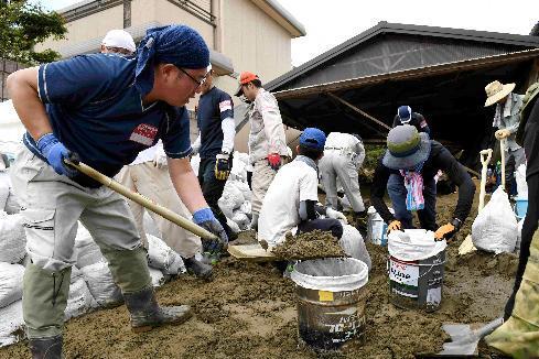 住宅の駐車場に積もった土砂を集めるボランティアの人たち=7月14日午後、福岡県朝倉市山田、長沢幹城撮影