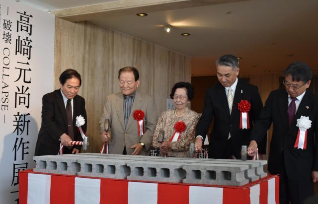 高﨑さんの作品にちなんで「テープカット」ではなく、「コンクリートブロック鏡割り」で開幕。中央が妻の佳恵さん=高知市